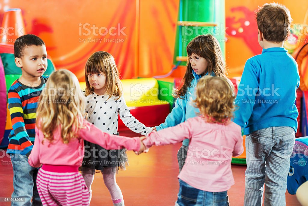 Group of children dancing in a circle. stock photo