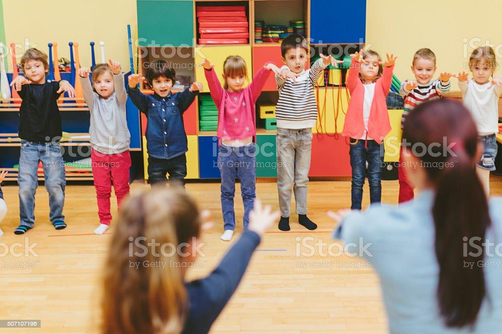 Group of children exercise with their teacher in kindergarten stock photo