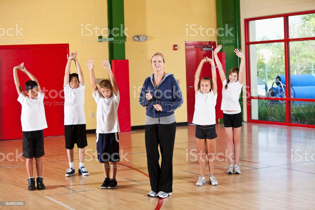 Group of children exercising with coach in school gym stock photo