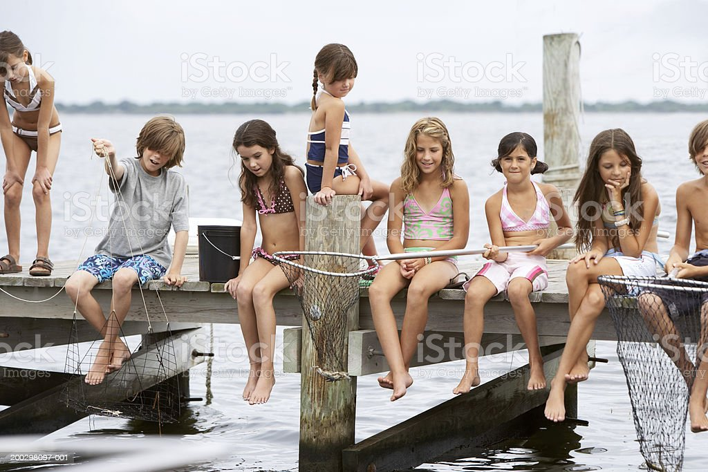 Group of children (5-12) fishing on jetty (Digital Composite) stock photo