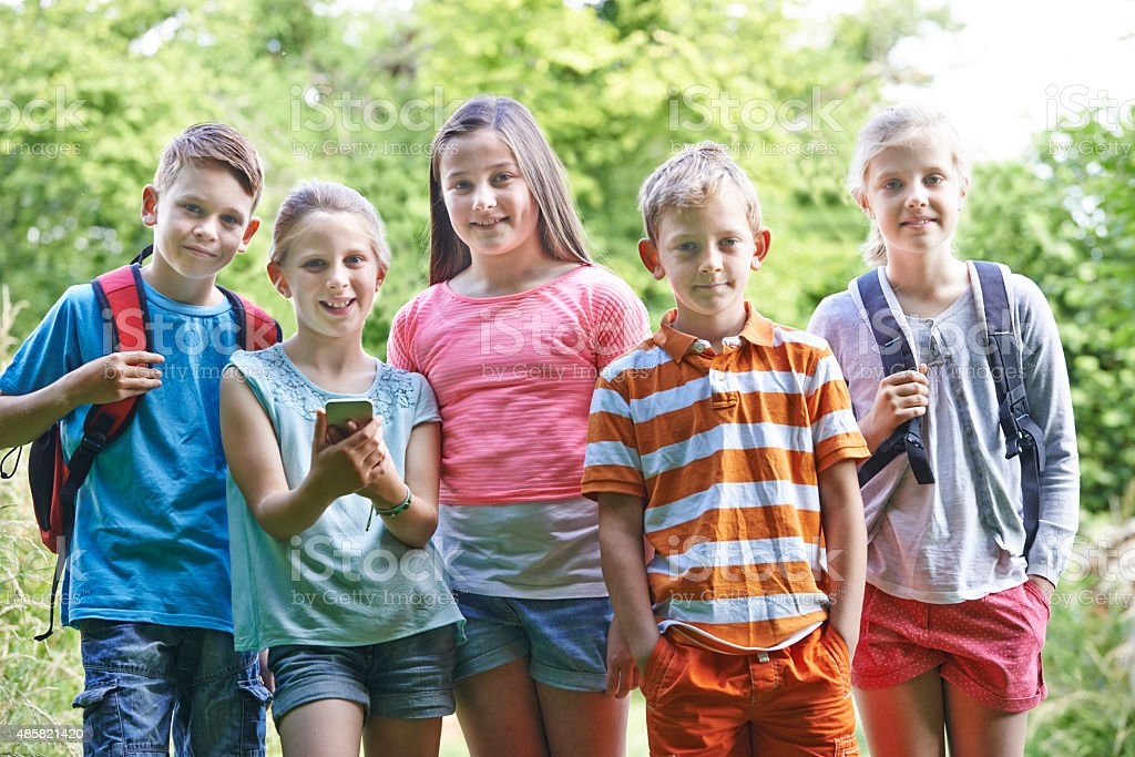 Group Of Children Geocaching In Woods stock photo