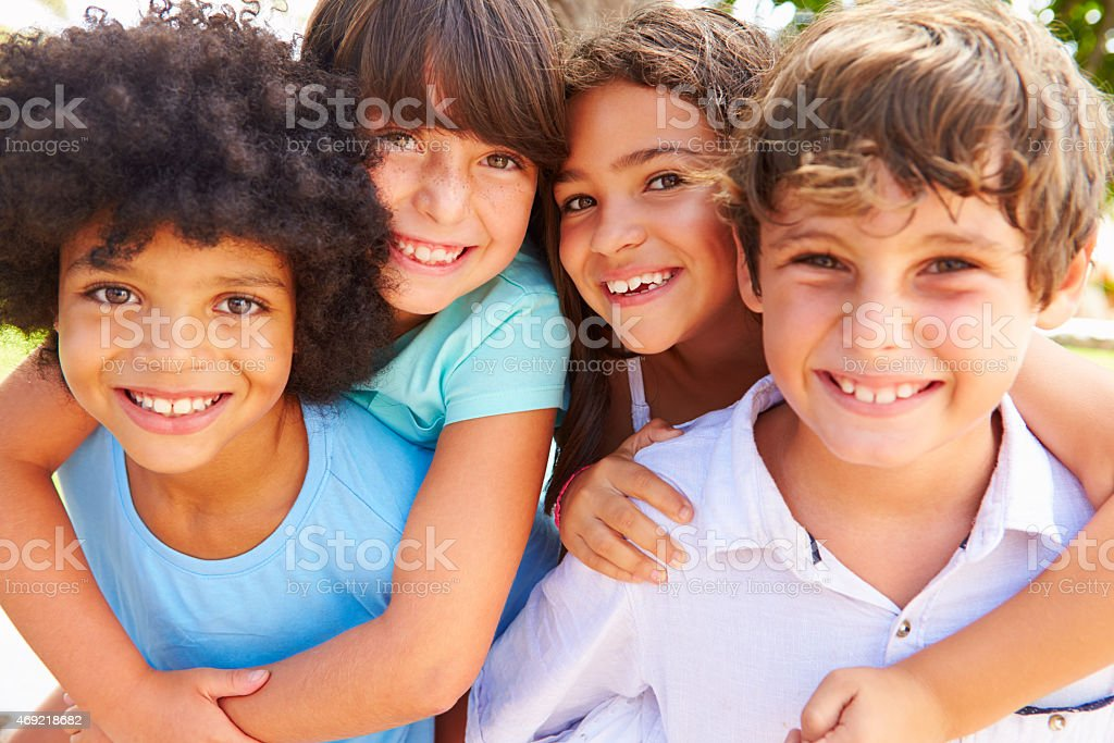 Group Of Children Giving Each Other Piggyback Rides stock photo