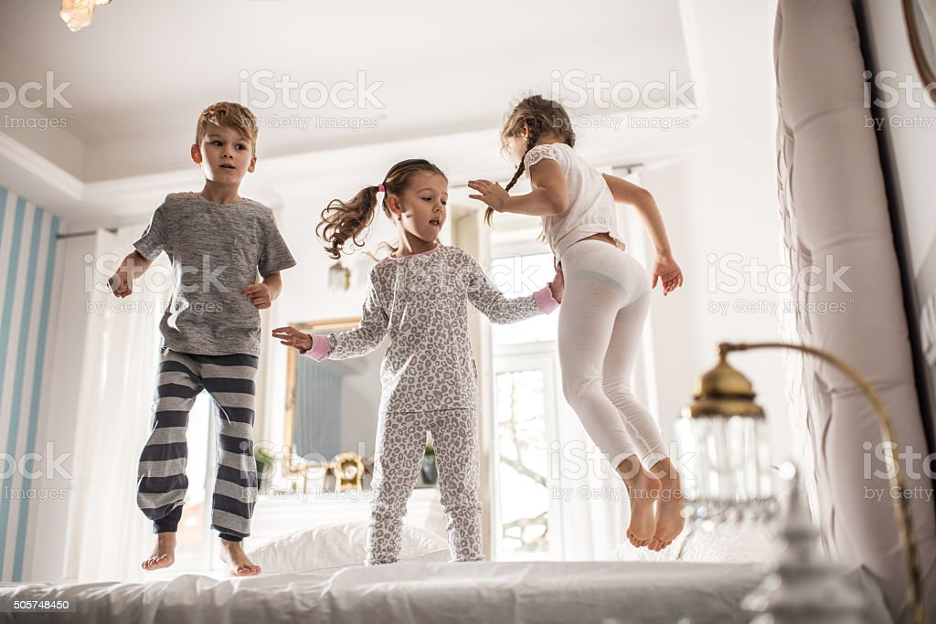 Group of children having fun while jumping on a bed. stock photo