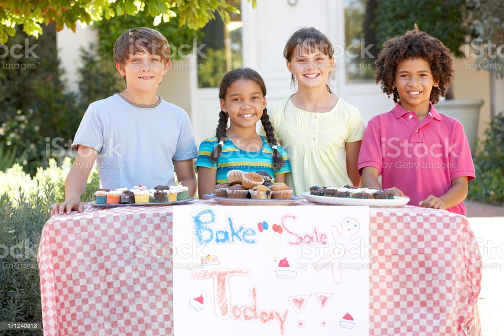 A group of children holding a bake sale stock photo