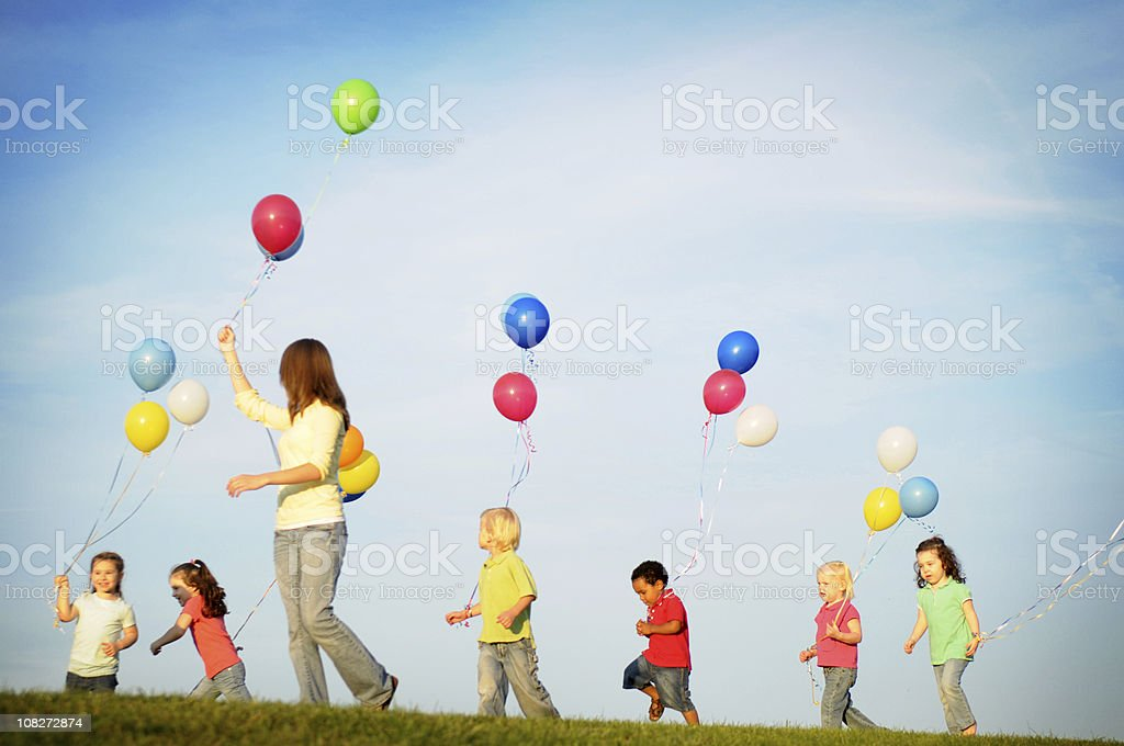 Group of Children Holding and Running with Balloons royalty-free stock photo