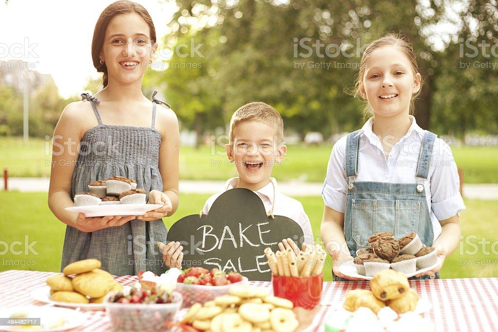 Group of children holding bake sale stock photo