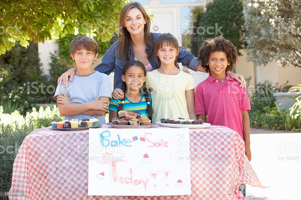 Group Of Children Holding Bake Sale With Mother stock photo