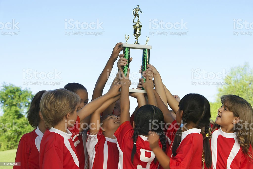 Group of children holding trophy above heads stock photo