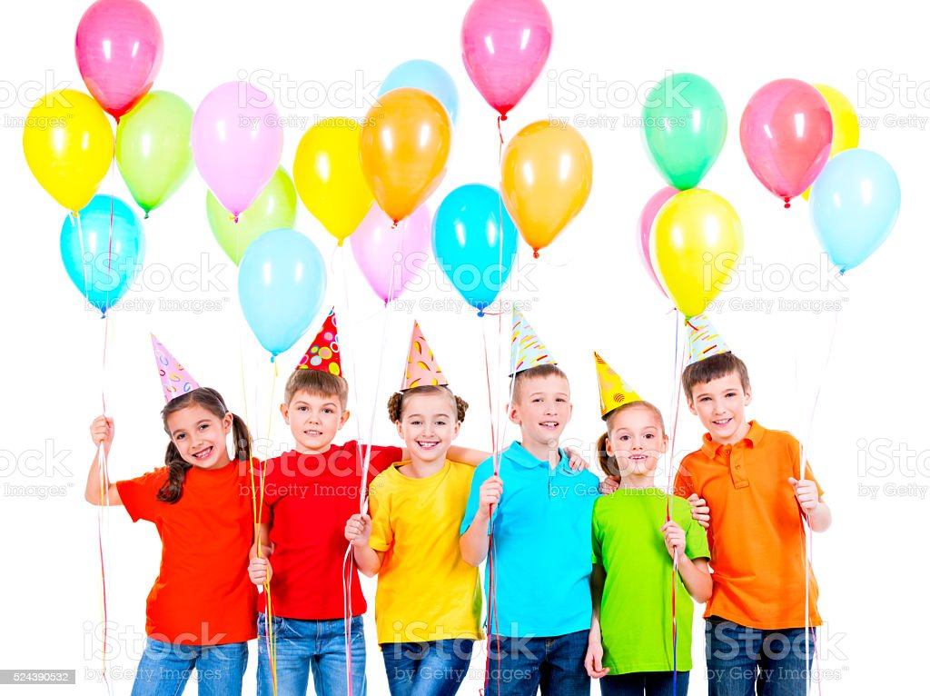 Group of children in colored t-shirts and party hats stock photo