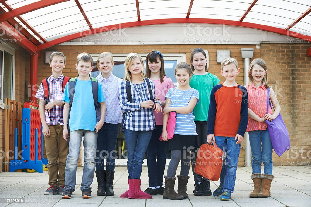 Group of children in front of school holding their bags stock photo