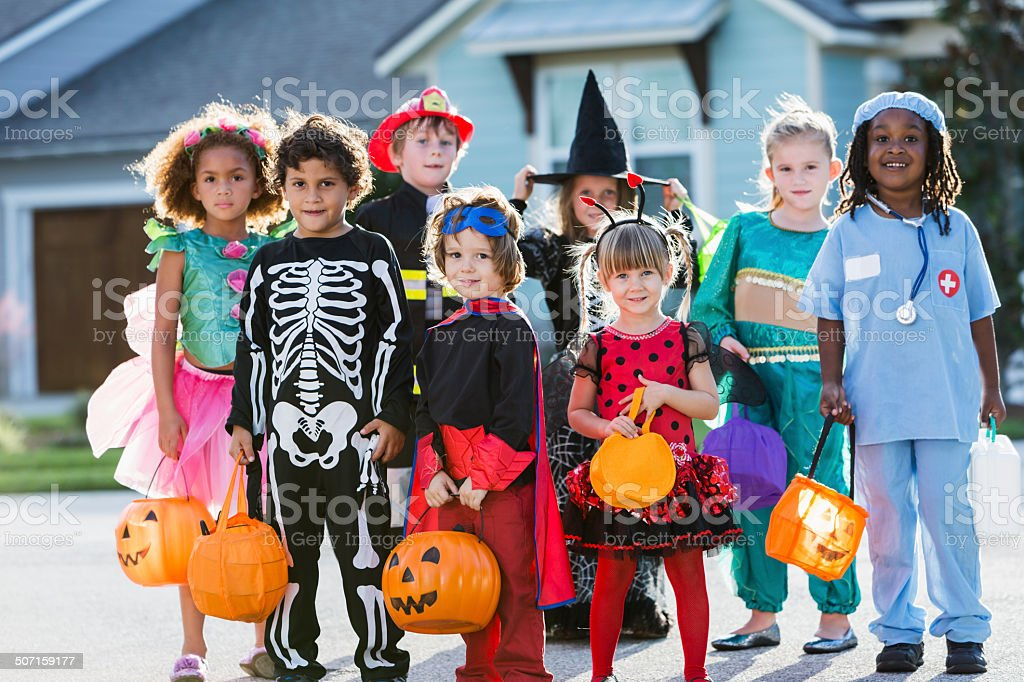 Group of children in halloween costumes standing outdoors stock photo