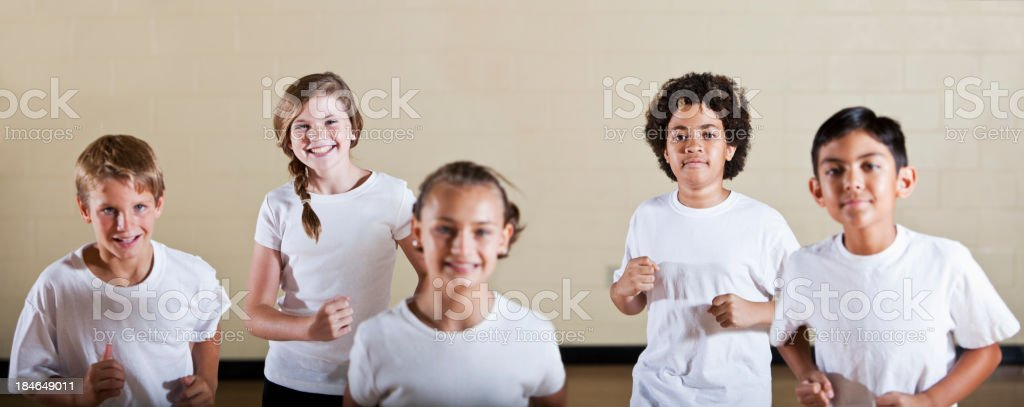 Group of children in phys ed class exercising stock photo