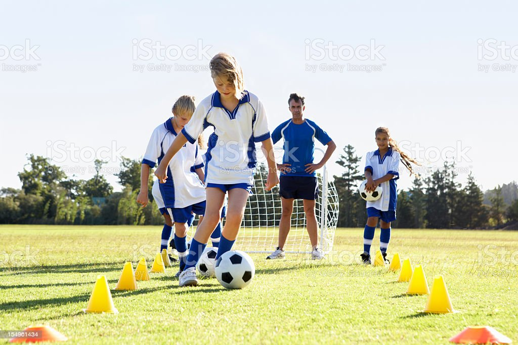 Group Of Children In Soccer Team Having Training With Coach royalty-free stock photo