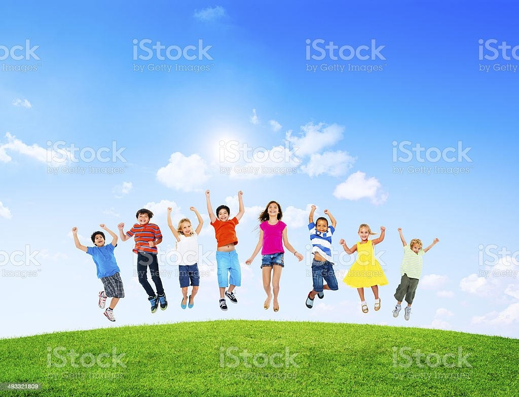 Group of children jumping on green lawn stock photo