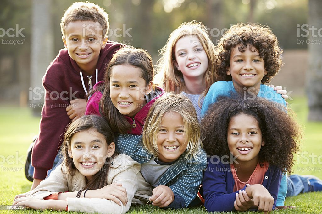 Group Of Children Lying On Grass Together In Park stock photo