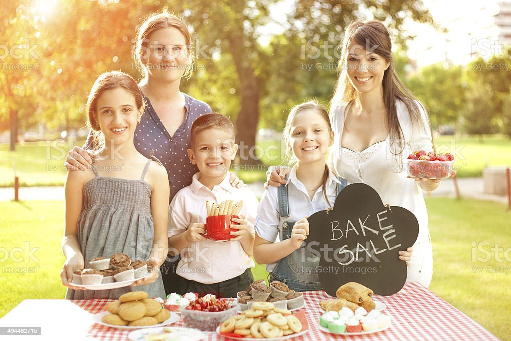 Group of children making bake sale with mothers stock photo