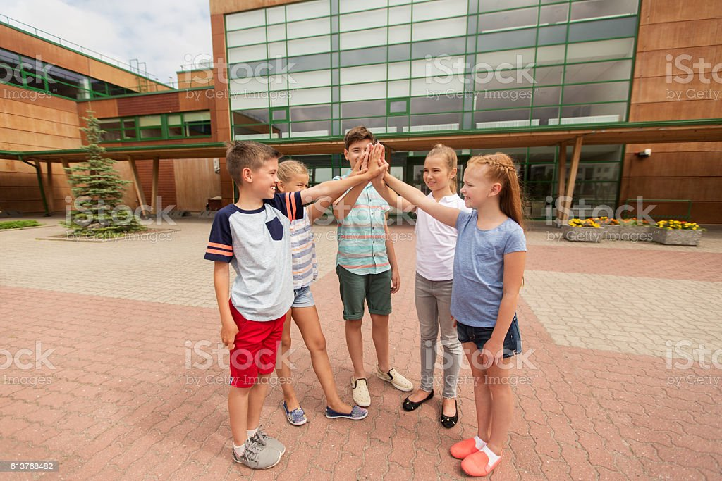 group of children making high five at school yard stock photo