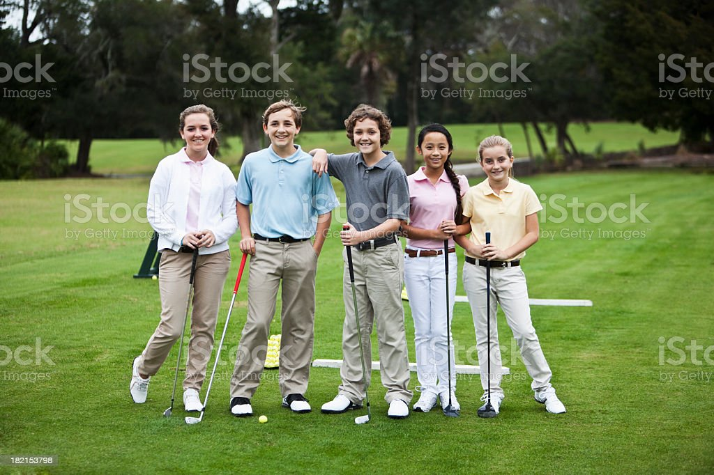 Group of children on golf driving range stock photo