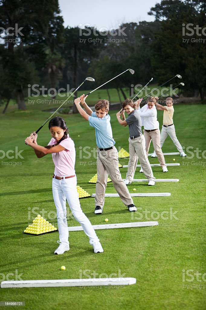 Group of children on golf driving range royalty-free stock photo