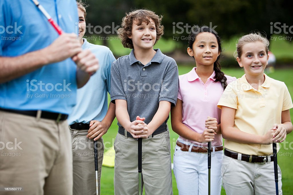 Group of children on golf driving range with instructor stock photo