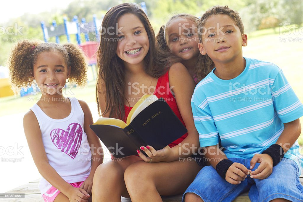Group of children outdoors around a girl with an open bible stock photo