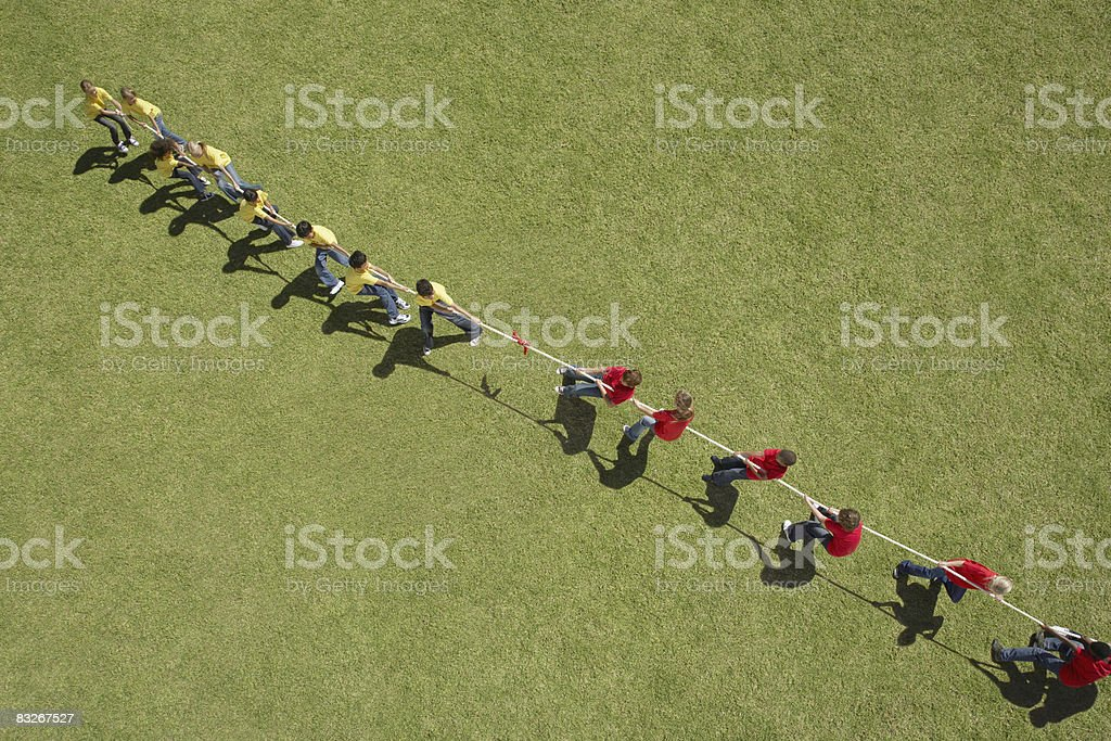 Group of children playing tug-of-war royalty-free stock photo