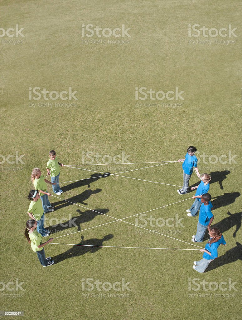 Group of children playing with string in park royalty-free stock photo
