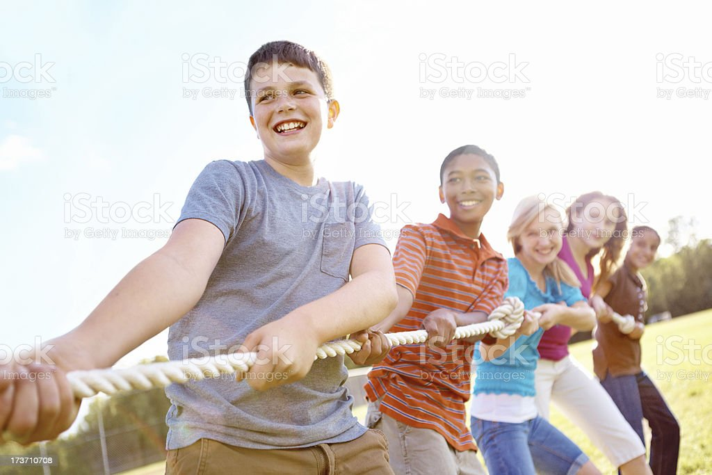 Group of children pulling rope in tug of war stock photo