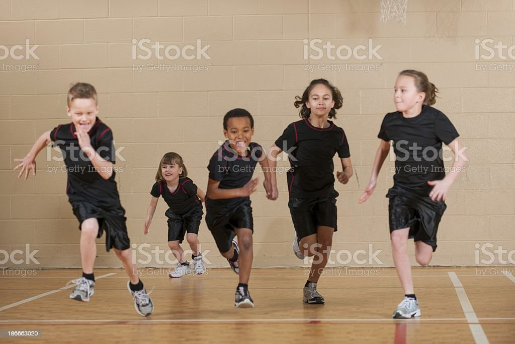 A group of children racing in a gym stock photo