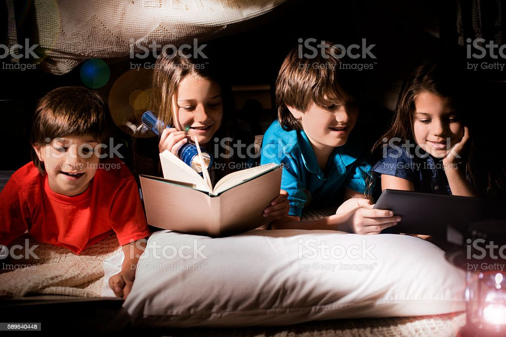 Group of children read together in homemade tent at home. stock photo