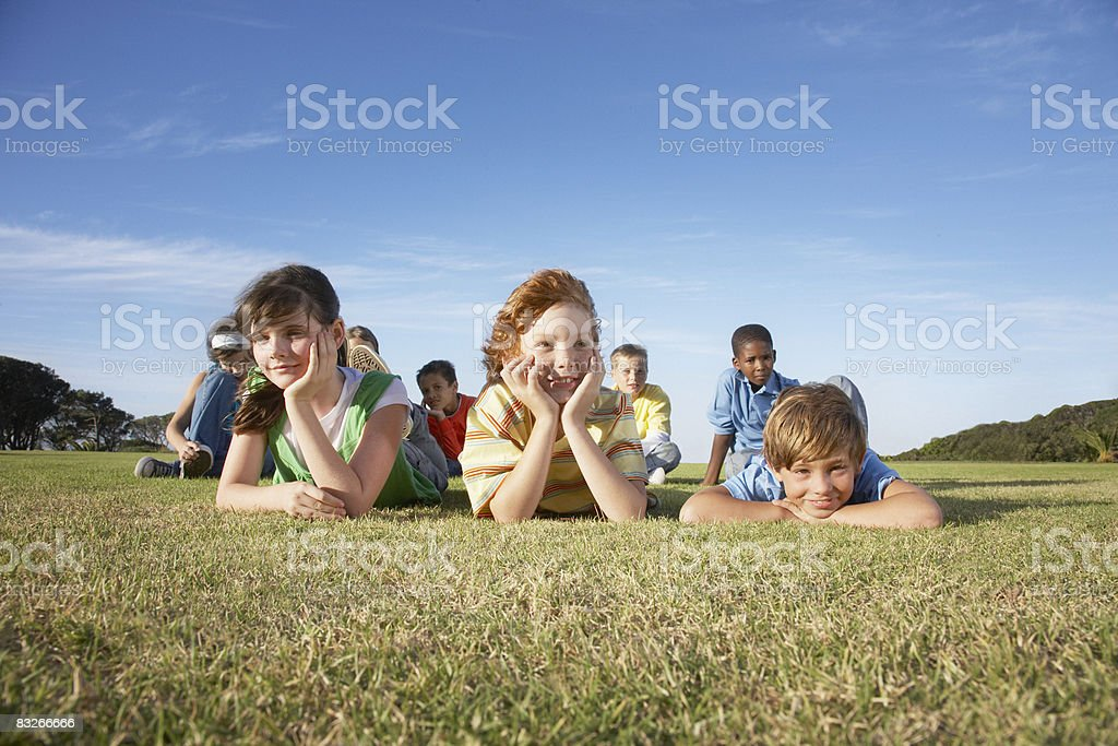 Group of children relaxing in grass royalty-free stock photo
