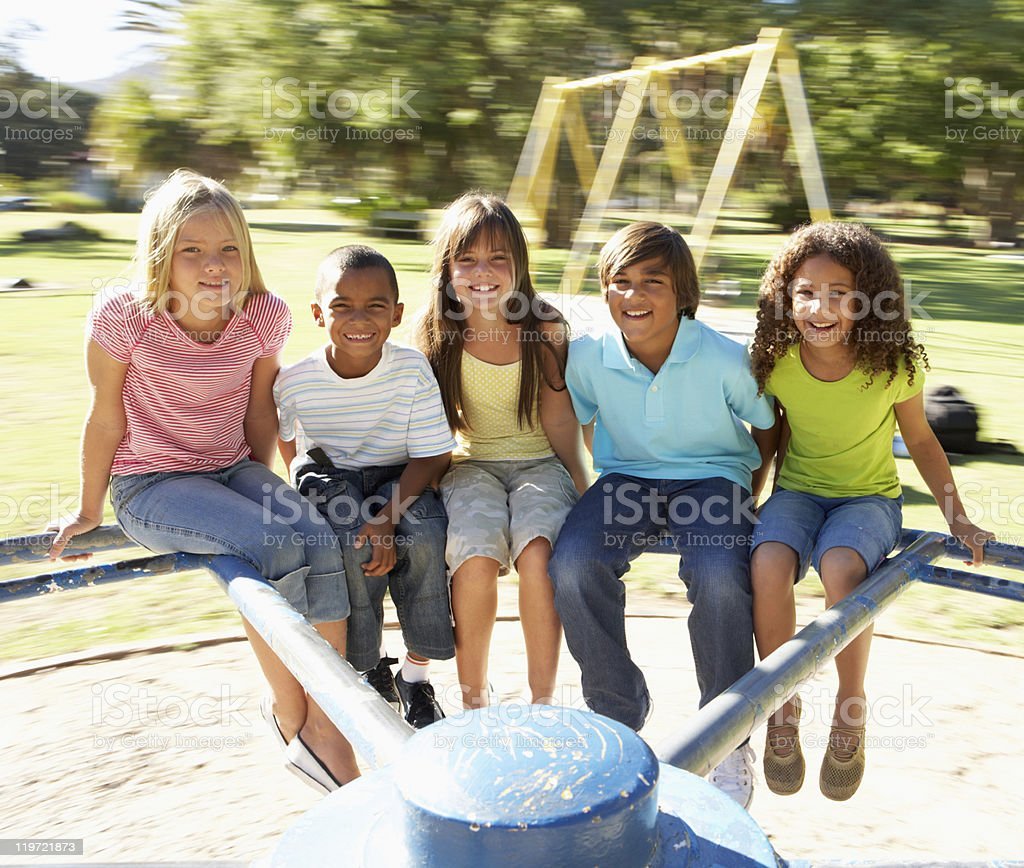 Group Of Children Riding On Roundabout In Playground royalty-free stock photo