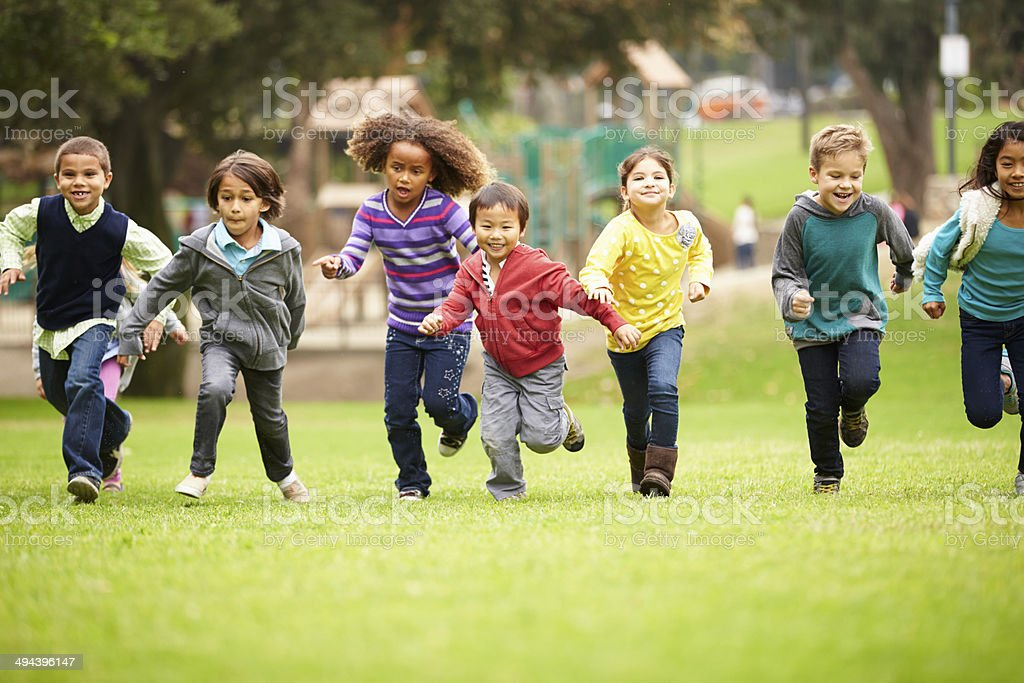 Group of children running over playground grass stock photo