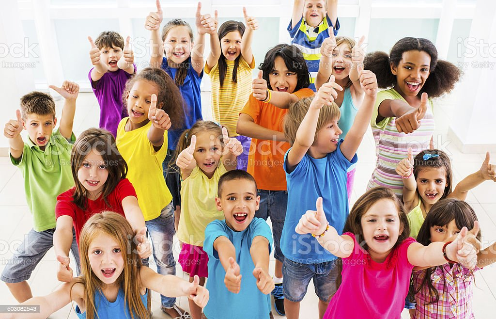 Group of children showing thumbs up. stock photo