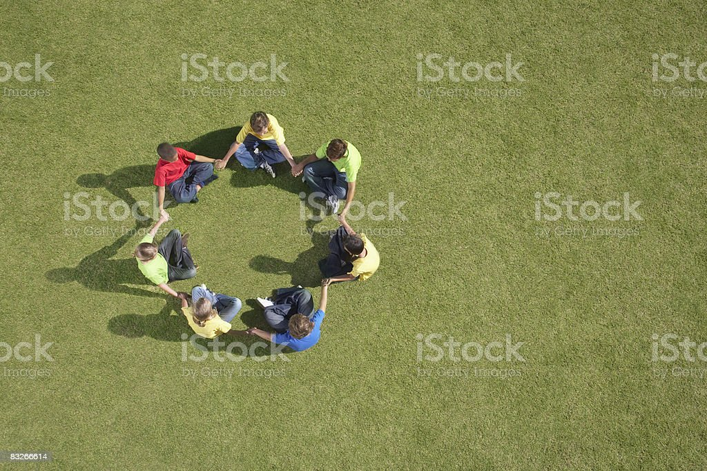 Group of children sitting on grass in circle formation stock photo