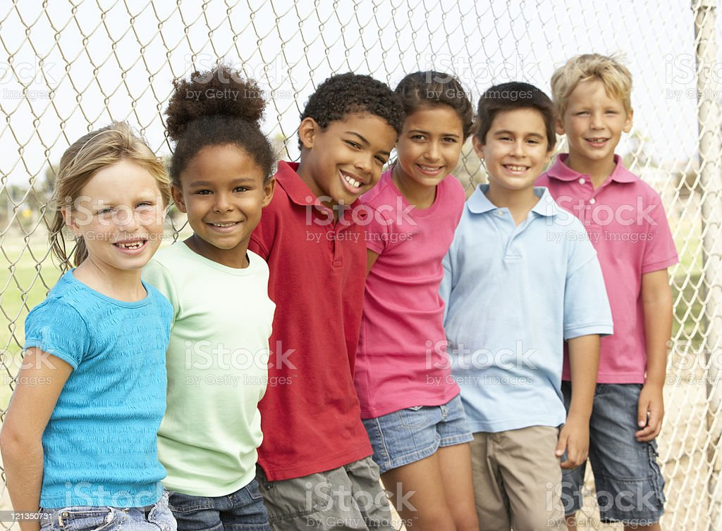 Group of children standing by chain link fence in park stock photo