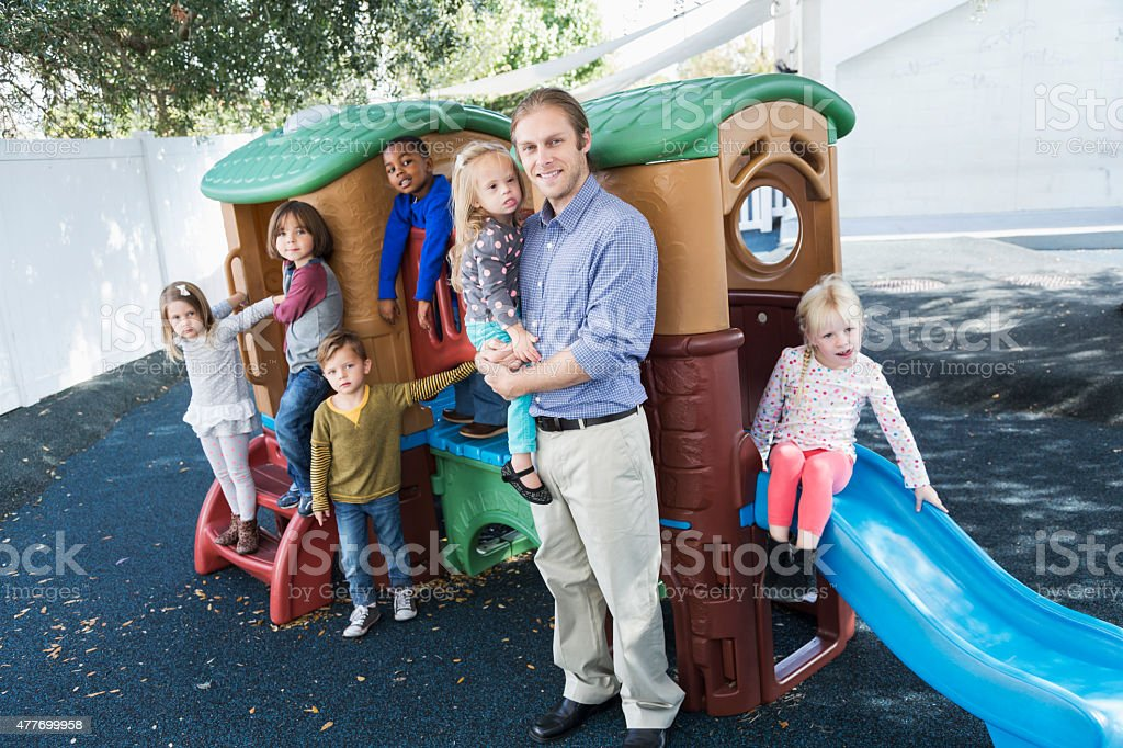 Group of children with adult at preschool playground stock photo