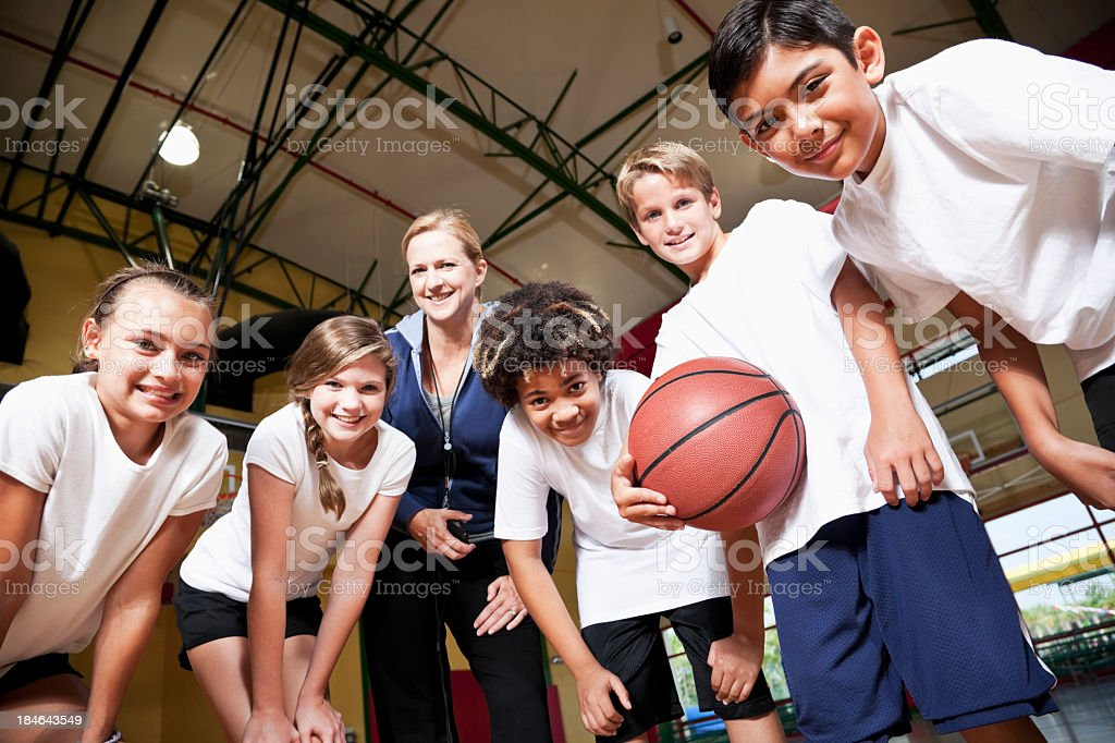 Group of children with coach playing basketball stock photo