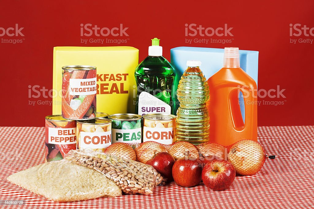 Group of cleaning products and basic foods on kitchen table royalty-free stock photo