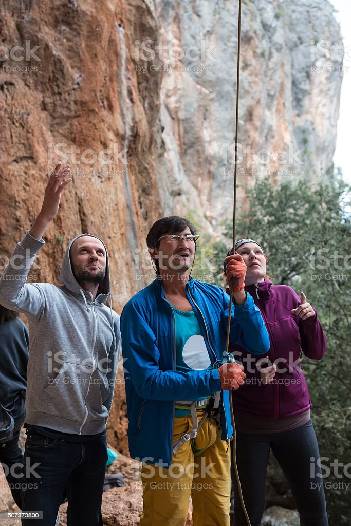 Group of Climbers belays Leader with Mature Coach in middle stock photo
