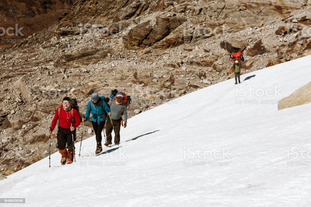 Group of Climbers walking on Snow Nepalese Porter on Background stock photo