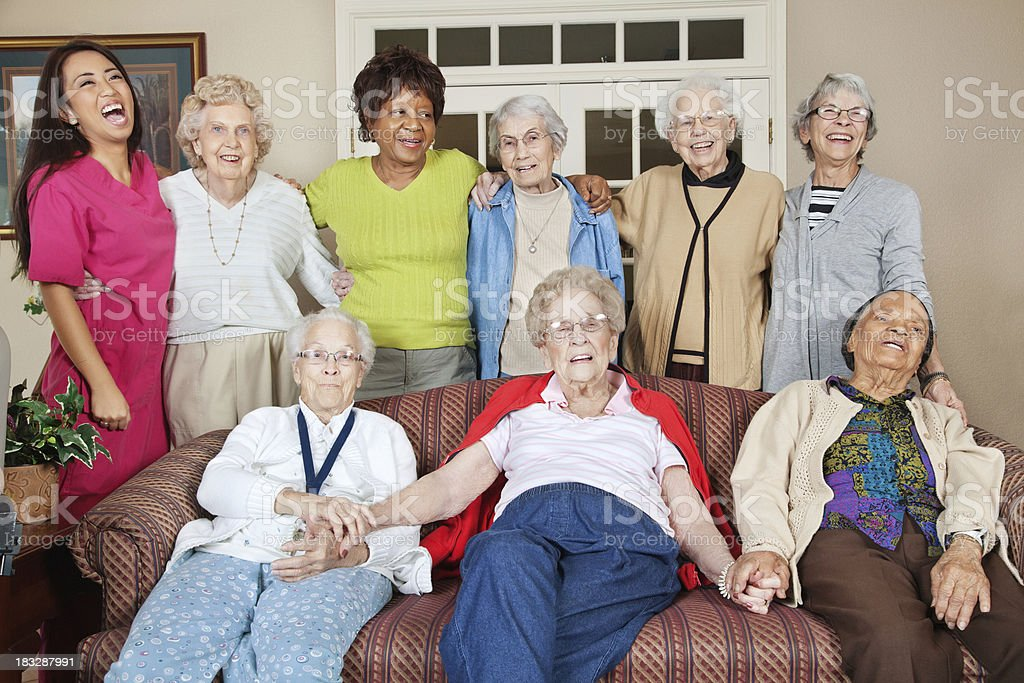 Group of Close Seniors With Caretaker in Living Area royalty-free stock photo