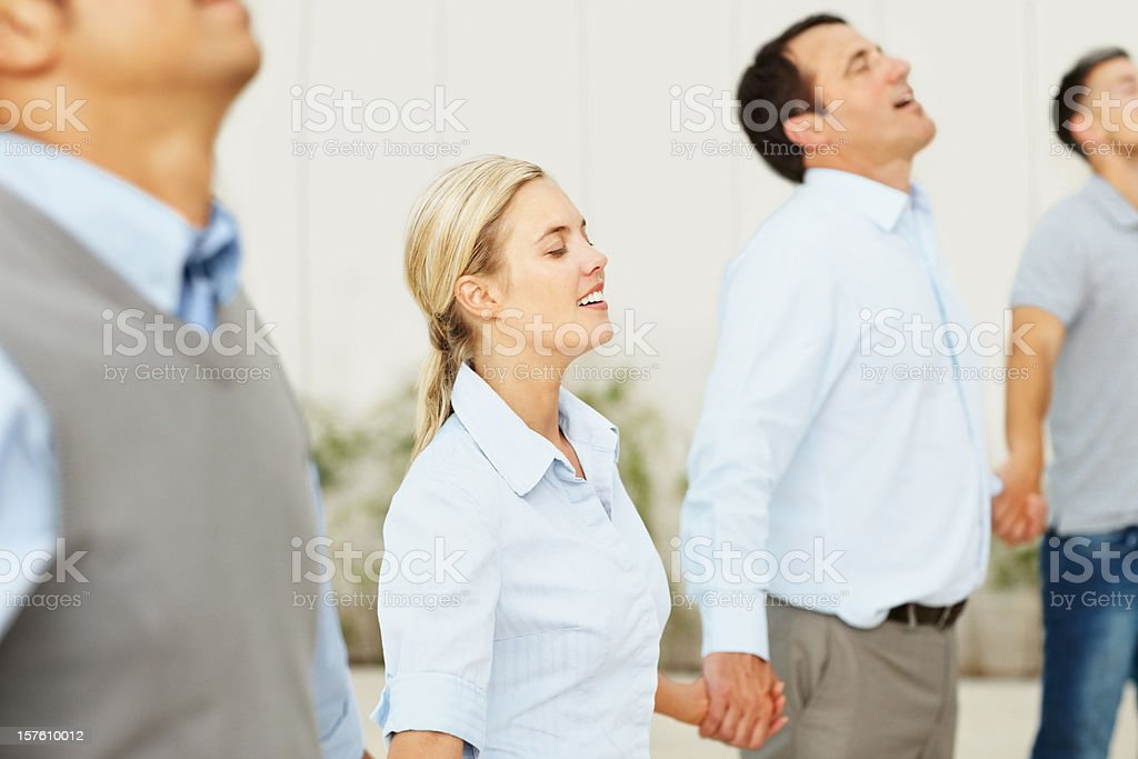 Group of colleagues holding hands in line with eyes closed royalty-free stock photo