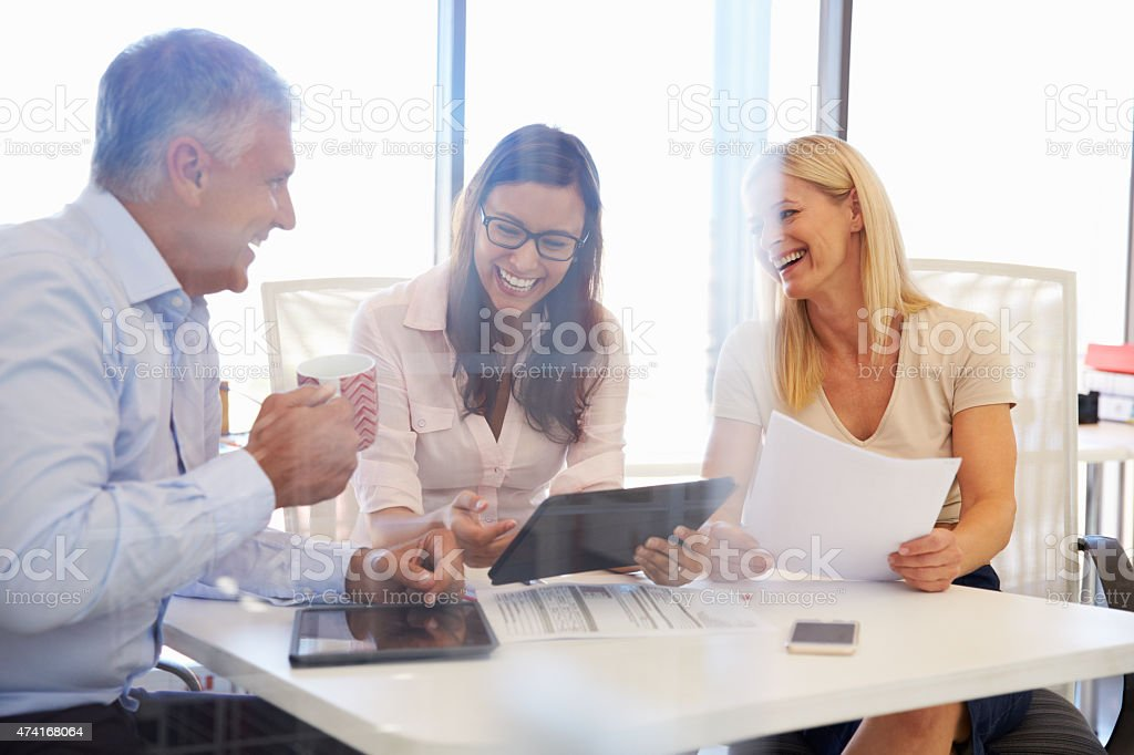 Group of colleagues meeting around a table in an office stock photo