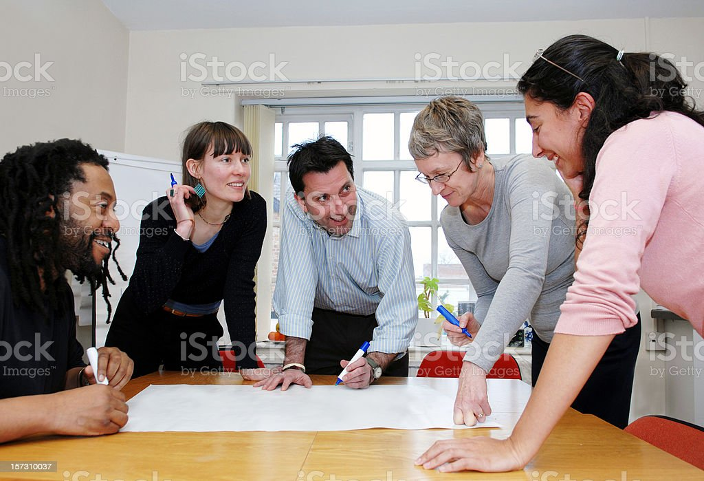 Group of colleagues on a meeting going over blueprints royalty-free stock photo