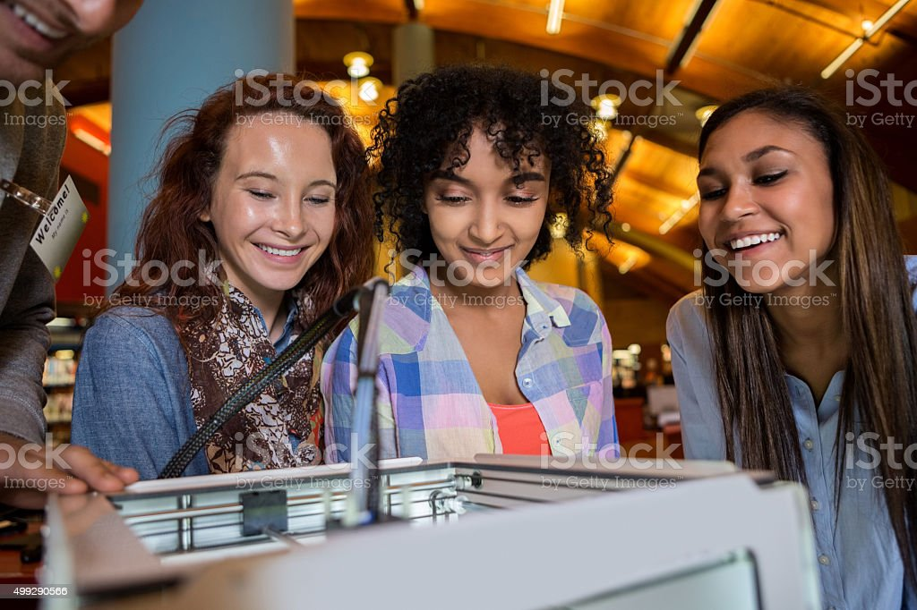 Group of college girls using 3D printer in library stock photo