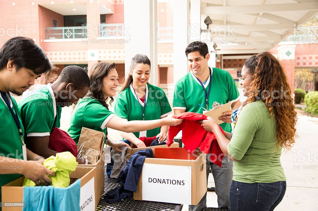 Group of college student volunteers collect clothing donations. Charity. stock photo