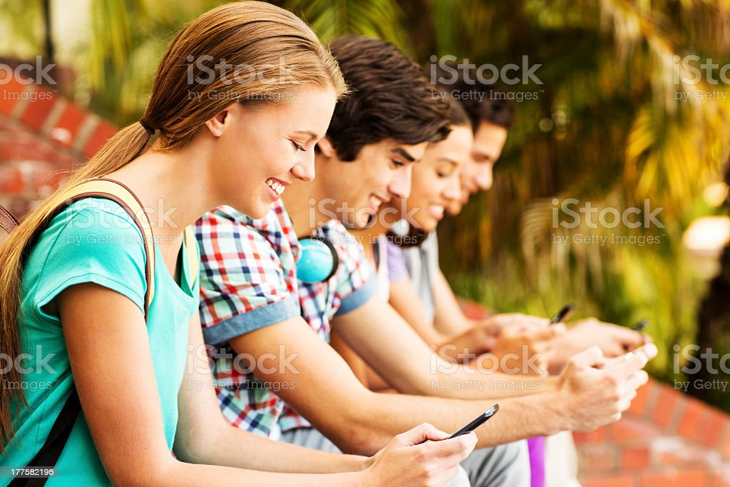 Group Of College Students Texting On Smart Phones At Campus royalty-free stock photo