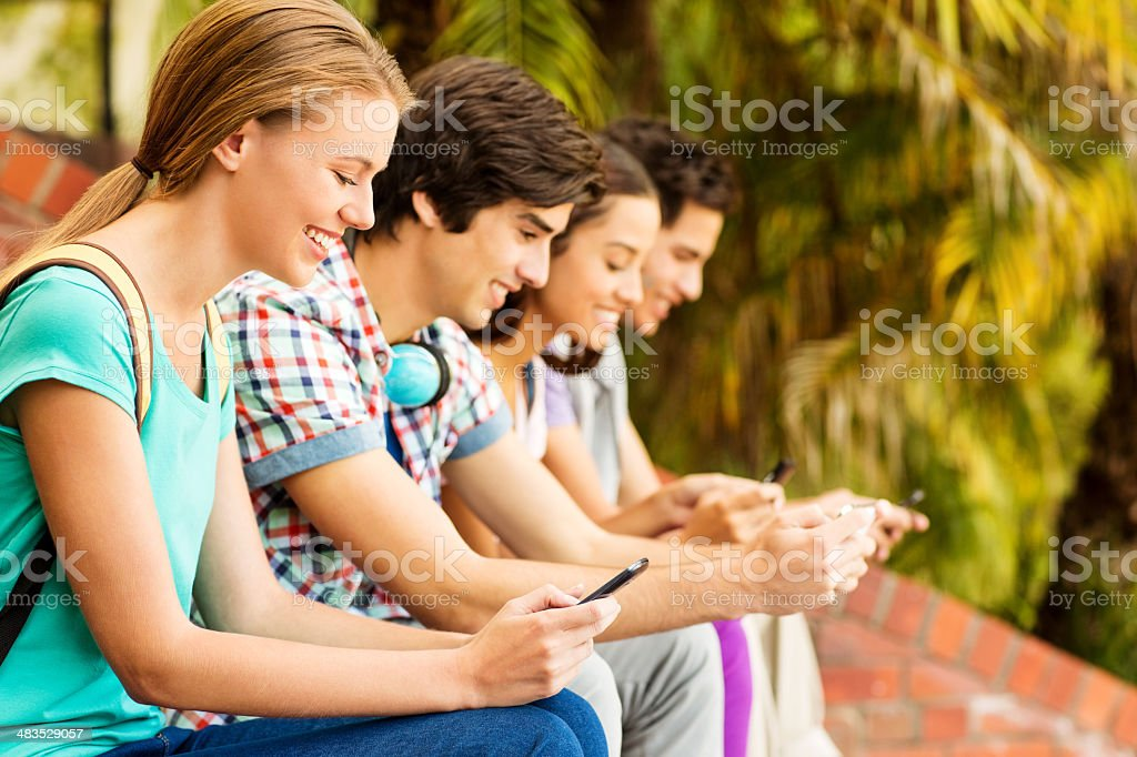 Group Of College Students Texting On Smart Phones royalty-free stock photo