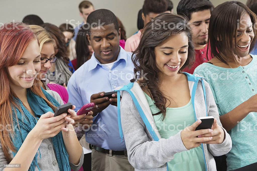 Group of college students using smart phones during event royalty-free stock photo